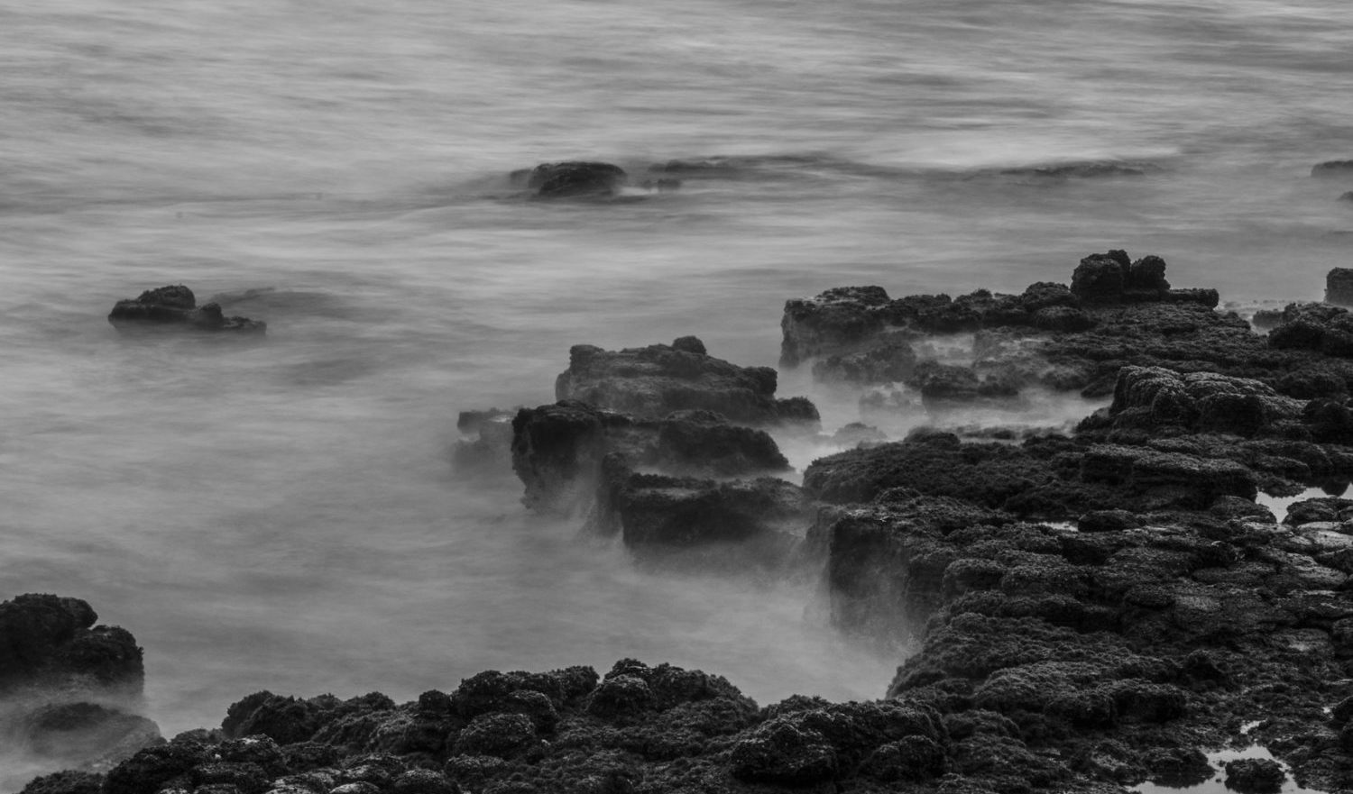 A long exposure black and white photo of blurred ocean waves splashing against lava rock on the coast of Maui, Hawaii