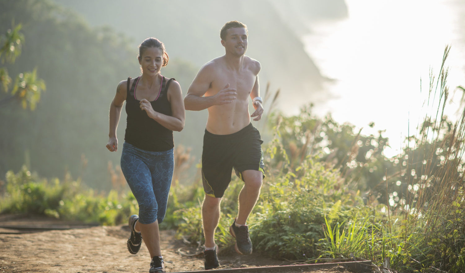 A boyfriend and girlfriend are trail running together in the Hawaiian mountains while on vacation.