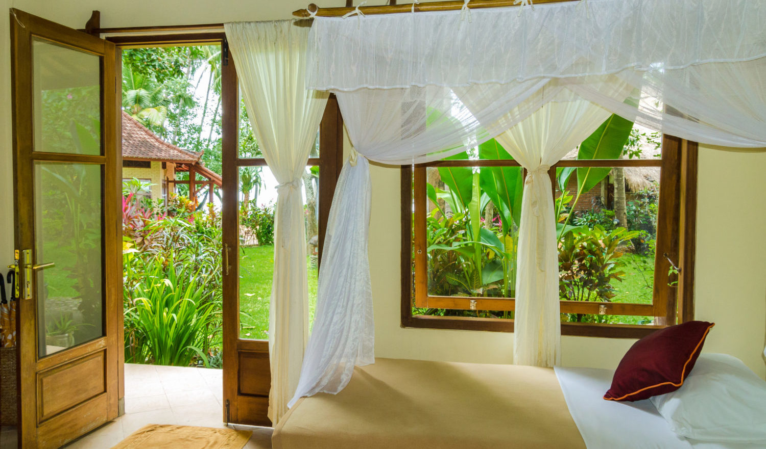 white curtains at a window. Behind the tropical jungle of Bali, Indonesia. View outside a resting room with bed and moskito net.