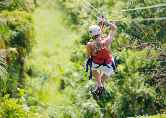 Woman enjoying a fun zip line tour in the jungle while on vacation