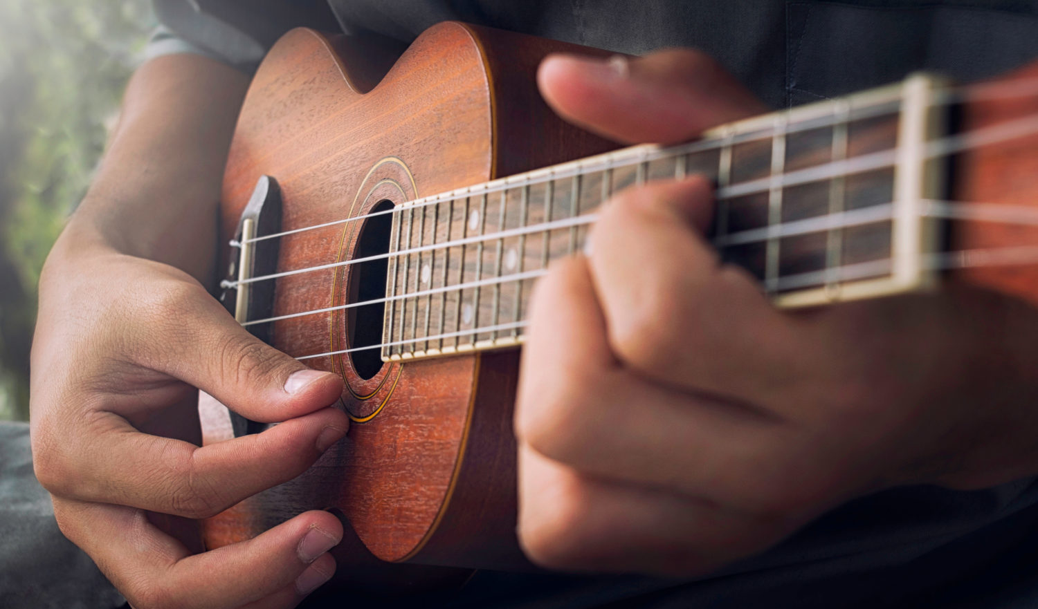 A man playing ukulele in close up view.
