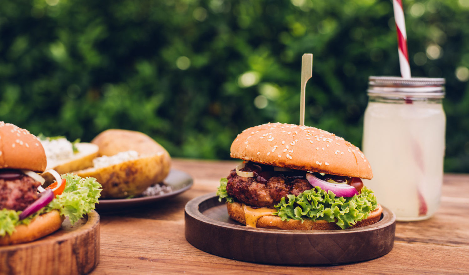 Gourmet cheese burgers with a beverage outdoors on a wooden table in a summery back yard