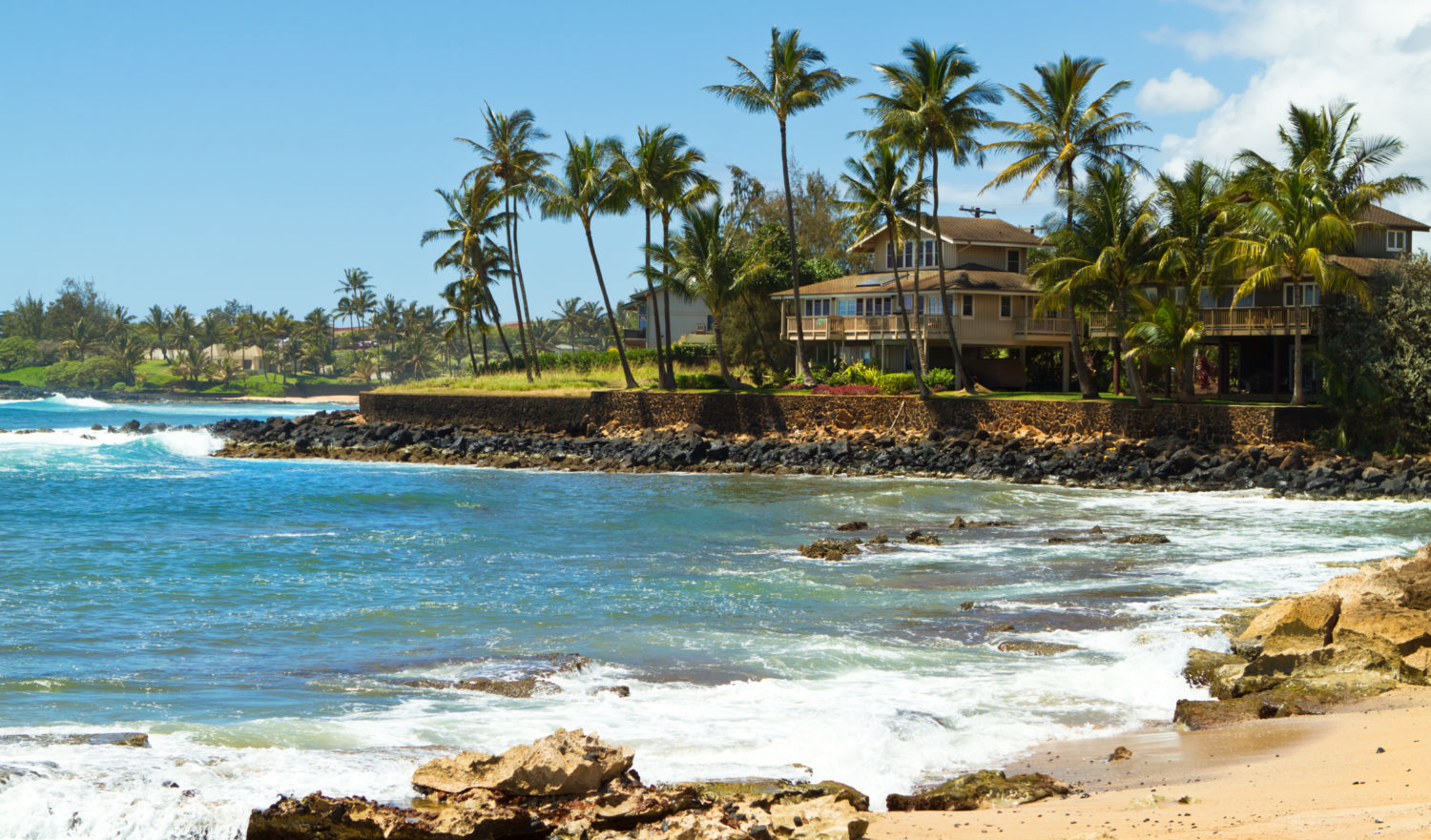 """House surrounded by tall palm trees facing the beautiful blue ocean and a sandy beach at south shore of Kauai, Hawaii on a gorgeous sunny, summer day in the tropicsCheck out my Hawaiian Lightbox with more images:"""