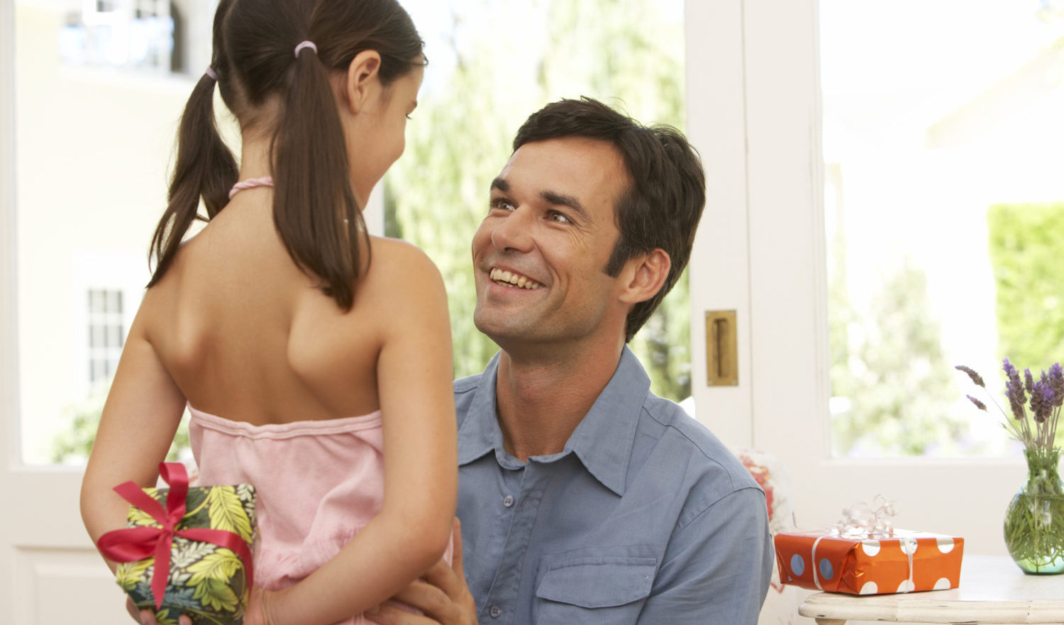 Girl (5-7) holding present behind back, standing by father