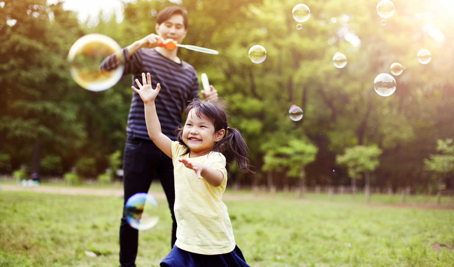 Japanese father and daughter having fun in park with Soap Bubbles in Tokyo, Japan. Image is taken during Tokyo Istockalypse 2015