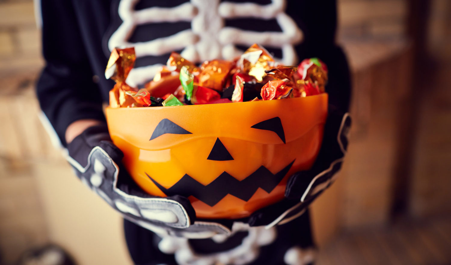Boy in skeleton costume holding bowl full of candies