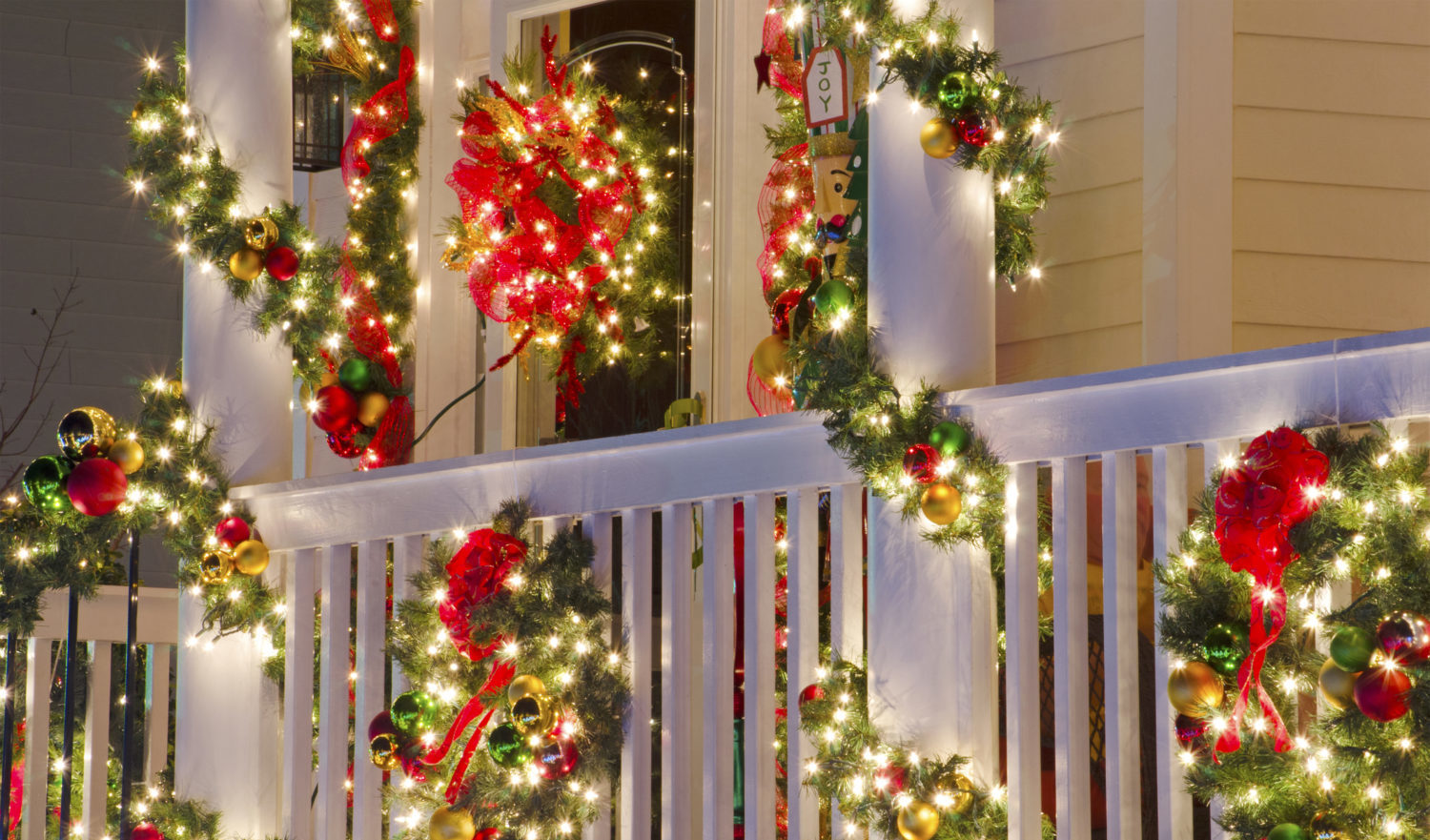 Close up detail of a Victorian-style home in a Christmas town/village that is beautifully decorated for the Holiday Season with lights, ornaments, wreaths and garlands.