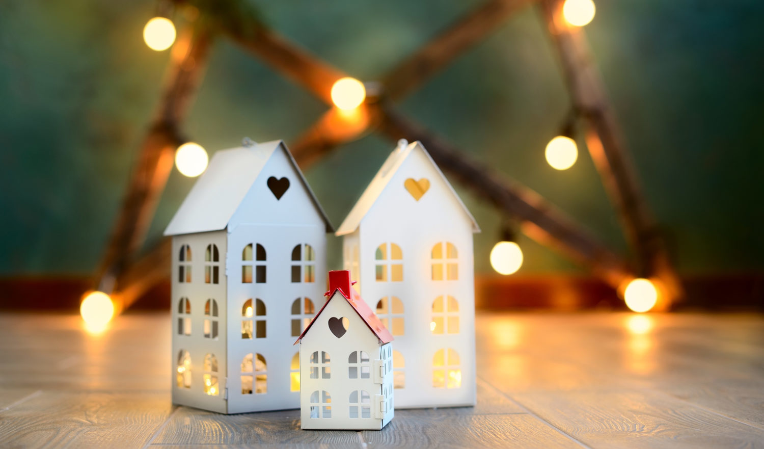 little toy Christmas houses with a burning light inside is on blured green background. Real estate, holiday, xmas, miniature